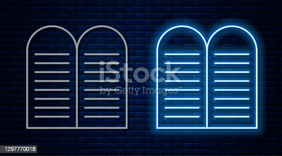 istock Glowing neon line The commandments icon isolated on brick wall background. Gods law concept. Vector 1297770018