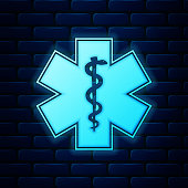 Glowing neon Medical symbol of the Emergency - Star of Life icon isolated on brick wall background. Vector Illustration