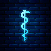 Glowing neon Rod of asclepius snake coiled up silhouette icon isolated on brick wall background. Emblem for drugstore or medicine, pharmacy snake symbol. Vector Illustration