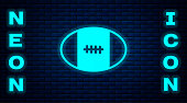 Glowing neon Rugby ball icon isolated on brick wall background. Vector.