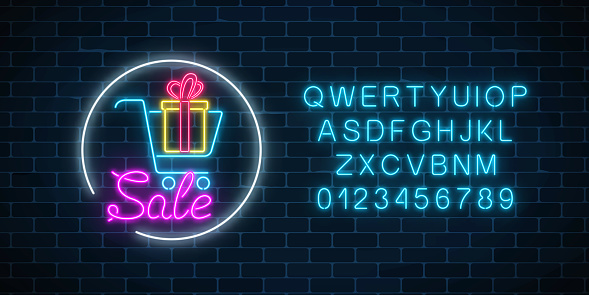 Glowing neon sign of supermarket shopping cart with gift box and alphabet. Luminous advertising sale banner.