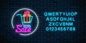 Glowing neon sign of supermarket shopping cart with gift box and alphabet on a dark brick wall background. Luminous advertising sale banner. Neon light effects store basket. Vector illustration.
