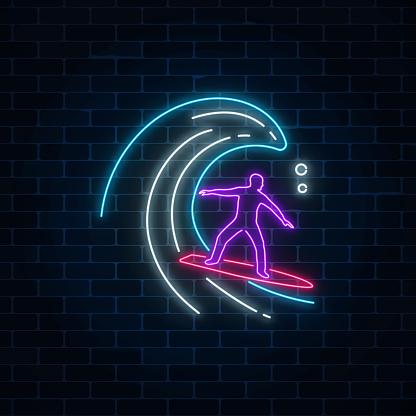 Glowing Neon Sign Of Surfer In Ocean Wave On Dark Brick Wall
