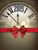 Gold shiny 2019 New Year background with clock and red satin ribbon with beautiful bow. Christmas greeting card template. Vector illustration.