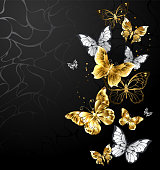 Gold, jewelry and white butterflies on black background.