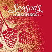 Branch of pine cones shape for the Christmas cut out from gold dust spreading over the red background