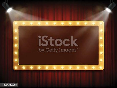 istock Gold frame with light bulbs on red velvet curtain. 1127332084