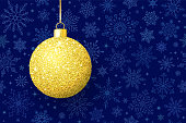 Christmas ball with gold glitter on dark blue background
