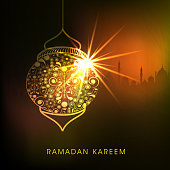 Golden floral design decorated shiny lamp on Islamic Mosque silhouette background for holy month of Muslim community Ramadan Kareem celebration.