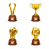 Golden trophies cups and awards on wooden stand