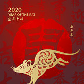 Celebrate the Year of the Rat 2020 with gold colored rat paper art and red stamp on the red Chinese language background, the red stamp means rat, the horizontal Chinese phrase means wish you luck in the year of the rat and the vertical Chinese phrase means Year of the Rat according to Chinese calendar