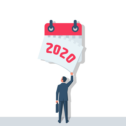 Goodbye 2020. A businessman tears off a calendar sheet of the outgoing year.
