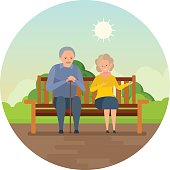 Grandparents are sitting on bench in park, smiling and speaking