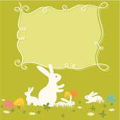 Easter white rabbits family and painted eggs on the grass design. Copy space for text.