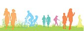 A vector silhouette illustration of different lifestyles in bright colours outside on green grass.  A mother walks with her young daughter, a father rides his bicycle with his son, a woman walks alone, two young couples walk holding hands, and another woman wears a long dress/