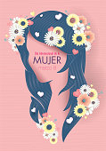 Greeting Card of DIA INTERNATIONAL DE LA MUJER - INTERNATIONAL WOMEN S DAY in Spanish language. Silhouette of woman head with long blue hair decorated with hearts, white and yellow flowers on pink background