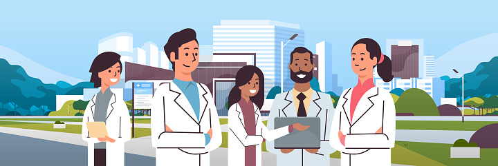 Group Of Mix Race Doctors Team In Uniform Standing Together Over Hospital Building Modern Medical Clinic Exterior Cityscape Background Portrait Flat Horizontal Stock Illustration - Download Image Now