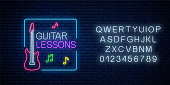 Guitar lessons glowing neon poster or banner template with alphabet. Guitar training advertising flyer in neon style on dark brick wall background. Vector illustration.