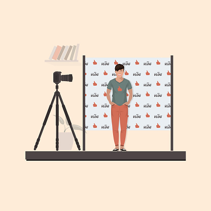 Guy vloglogger in a T-shirt, sneakers in front of the camera on a tripod. Behind the back seamless pattern filming