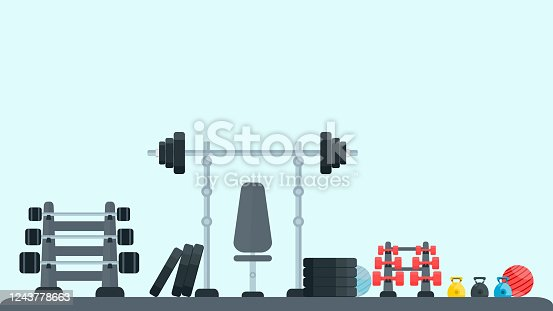 Gym fitness equipments; weight, dumbbell, kettlebell, pilates ball, barbell and bench in gym. Healthy lifestyle exercise and sports concept. Light blue background.