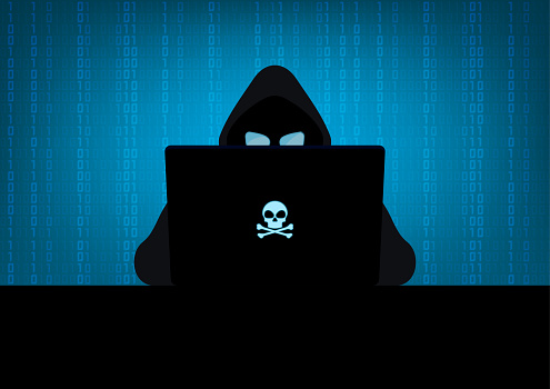 Silhouette of hacker wearing hood using laptop computer with glow in the dark blue skull and crossbones logo in dark room on blue binary code number background