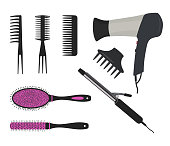 Hair dryer, a curling iron and different types of hair brushes on a white background