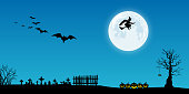 Black silhouettes of dead trees, fence, tombs, pumpkins, flying bats and witch against a blue night sky with full moon.