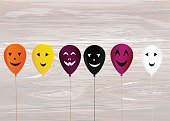 Halloween. Balloons with faces for a holiday, birthday and a party. Multicolored inflatable balls. Complimentary ticket. Free space for text or text. Vector on wooden background.