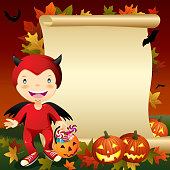 Little boy dress up devil costume in front of blank scroll on Halloween asking for candy or other treats.