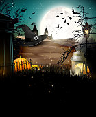 Halloween poster with pumpkins and other traditional Halloween decorations in front of a night landscape. Place for your text.