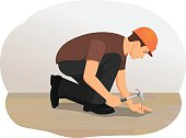 Handyman hammering a nail into wood. Installing wooden flooring.