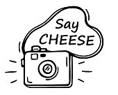"""istock Hand drawn a сute photo camera and the inscription """"Say CHEESE"""" in doodle style. Take photos. Clip art vector camera icon. Cartoon sketch illustration. Black lines isolated on a white background. 1302241497"""