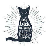 """Hand drawn Halloween label with textured black cat vector illustration and """"May luck be yours on Halloween"""" lettering."""