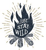 """Hand drawn inspirational label with textured bonfire vector illustration and """"Just stay wild"""" lettering."""