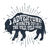 """Hand drawn tribal badge with textured buffalo vector illustration and """"Adventure awaits out in the wild, wild west"""" lettering."""