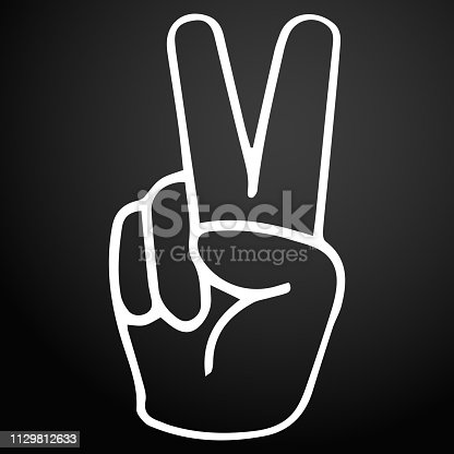 Hand gesture victory symbol on a dark background.