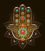 Esoteric, oriental symbol hand Hamsa of gold with turquoise and jasper on black background.