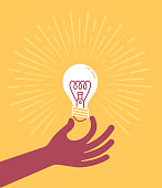 Hand holding a light bulb thought, intelligence, brainstorming and invention concept illustration.