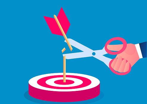 Hand holding scissors to cut the arrow that hit the bullseye
