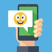Hand holding smartphone with happy emoji message on screen. Happy emoticon icon. Social networking, IM, SMS, instant messaging on mobile device, online chat concepts. Modern flat design vector illustration