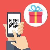 Hand holding smartphone with QR code on screen and gift