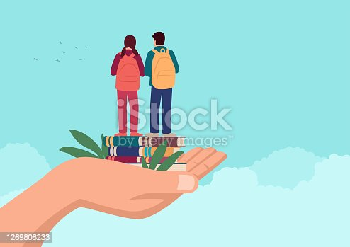 istock Hand holding two children standing on books with school backpack 1269808233