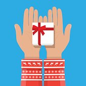 Hand holding white gift box with red bow