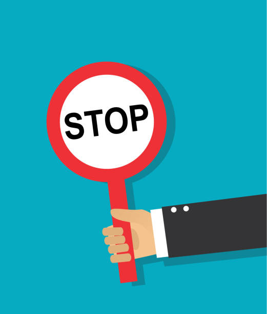 hand holds a round stop sign - stop sign stock illustrations