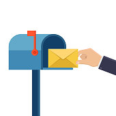 Hand holds letter and inserts it into mailbox