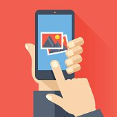 Hand holds smartphone with photos icon. Photo app. Vector illustration