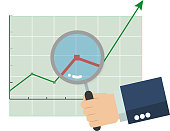 Hand of business man holding a magnifying glass and focus on graph