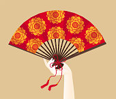 A hand of geisha holding a red fan with floral pattern, isolated.