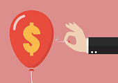 Hand pushing needle to pop the dollar sign balloon. Business concept