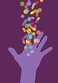 Silhouettes of hand reaching for pills and capsules.